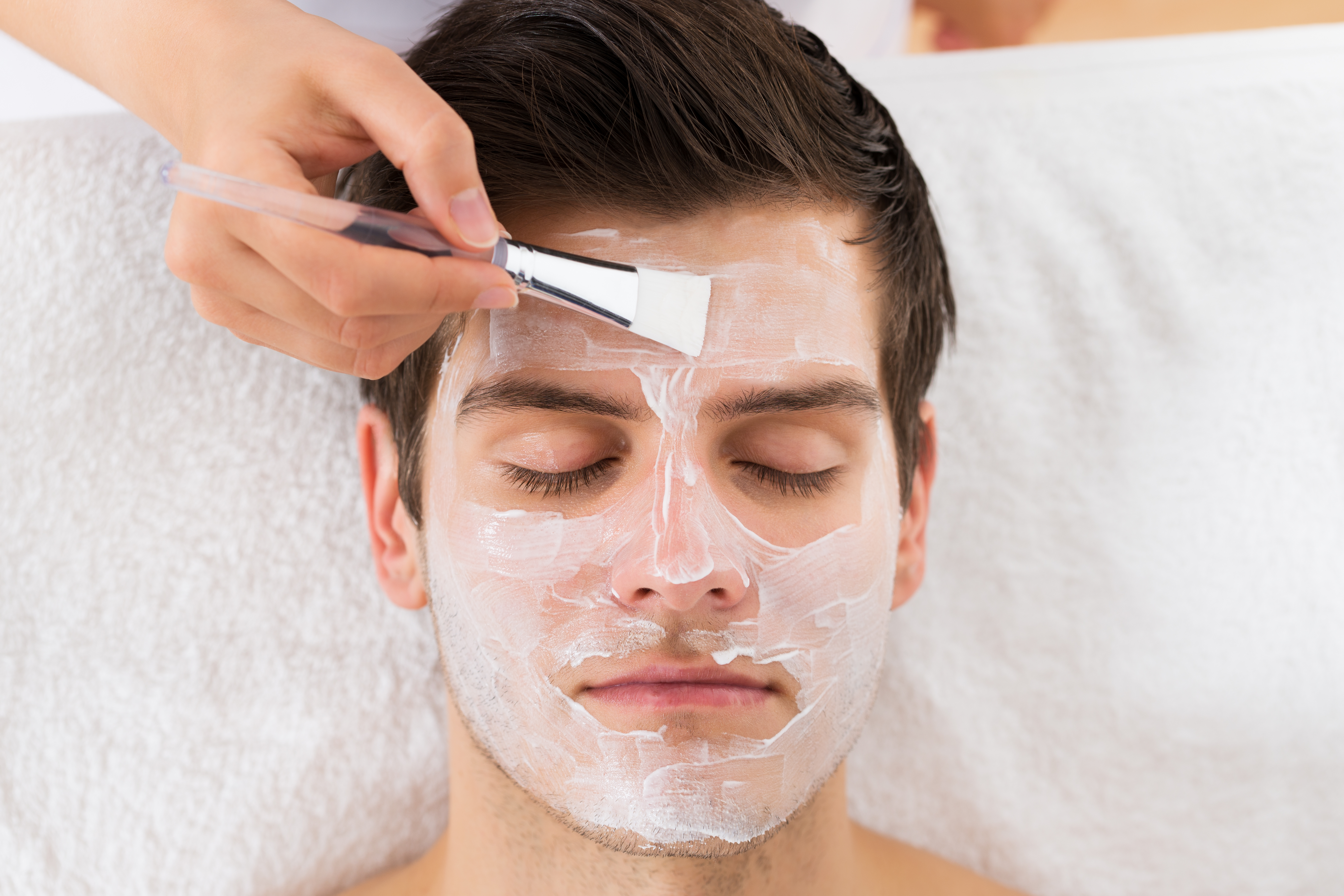 Therapist Hands With Brush Applying Face Mask To A Young Man In A Spa