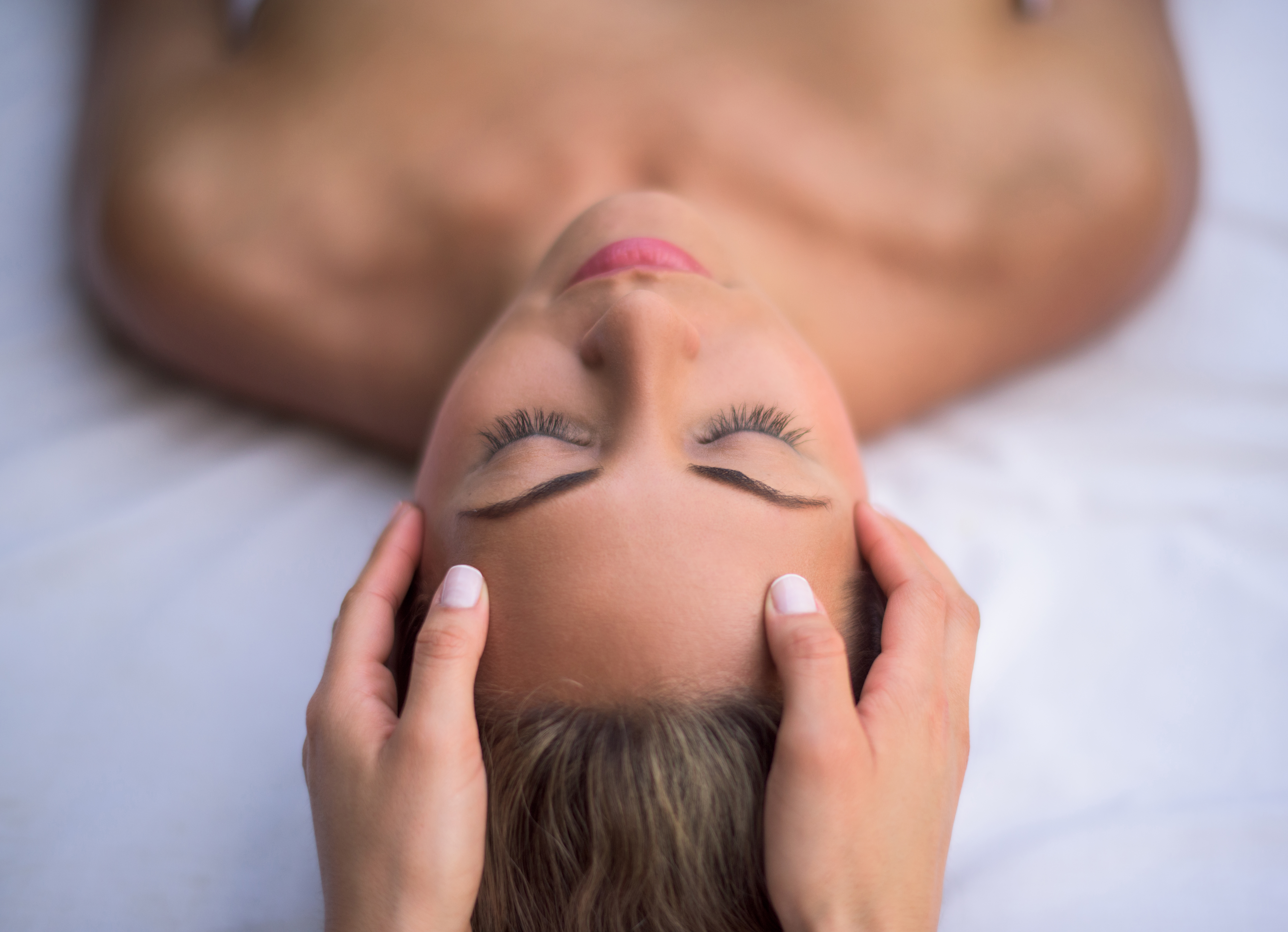 Beautiful woman getting a facial and relaxing at the spa - beauty concepts